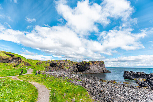 Tourists on a landscape trail hiking view of a rocky beach in Hellnar National park Snaefellsnes Peninsula in Iceland