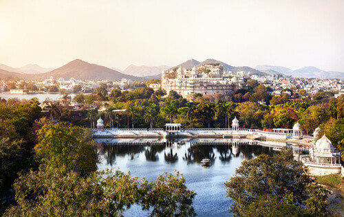 City Palace on Lake Pichola overlooking the Aravali Mountains in Udaipur India