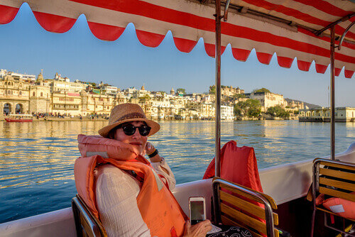Woman on a boat trip across Lake Pichola overlooking City Palace