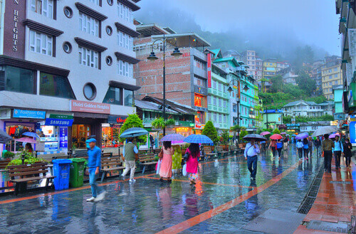 People walking in the MG Marg street carrying umbrellas during rain in Gangtok India