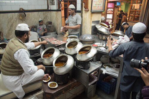 Indian man cooks curry in an old wok in a street market in Delhi India
