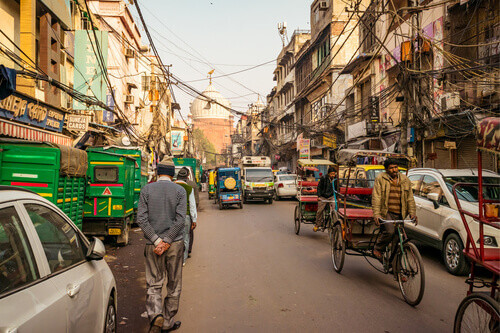 Rickshaws and car in Chandni Chowk market street with people and traffic at historical part of Old Delhi India