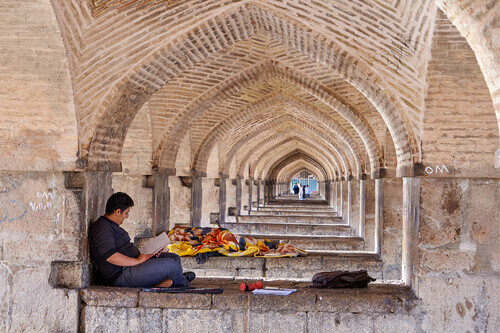 A young man reads notes in a notebook under Khaju Bridge in Esfahan Iran