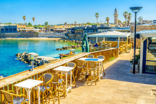 Beautiful outdoor restaurant in the harbour of Caesarea overlooks the buildings surrounding the port bright blue water and tiny beach in Caesarea Israel
