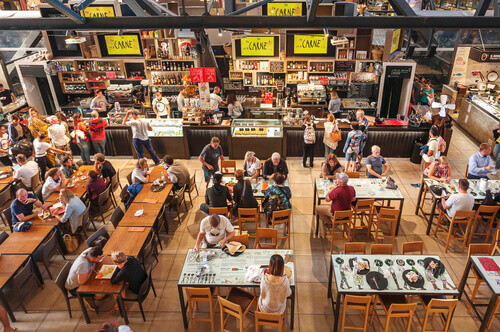 People having breakfast at popular food court inside Mercato Centrale city market in Florence Italy