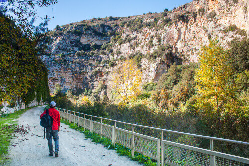 Hiker walking along the trails of the Anapo valley by the rocky necropolis of Pantalica in Sicily Italy