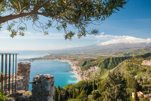 The village of Giardini Naxos and snowy Mount Etna seen from a viewpoint of the roman theater in Taormina in Sicily Italy