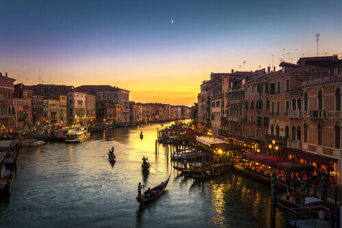 Famous Grand Canal view from Rialto Bridge at sunset in Venice Italy