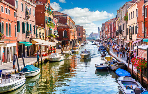 Island murano with a view on canal with boat and motorboat on water in Venice Italy