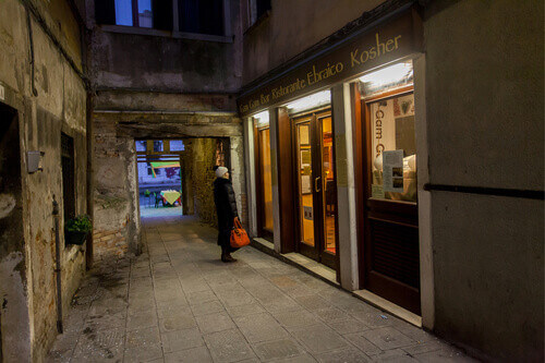 Woman looks into the shop window of the kosher Gam Gam Bar in the Jewish quarter in Venice Italy