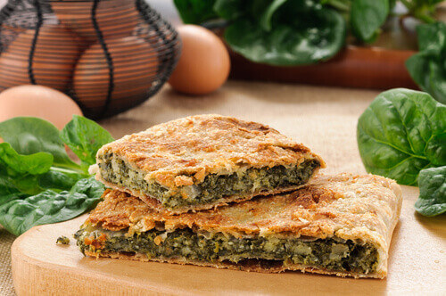 Erbazzone a savory spinach pie with cheese on a wooden board in Italy