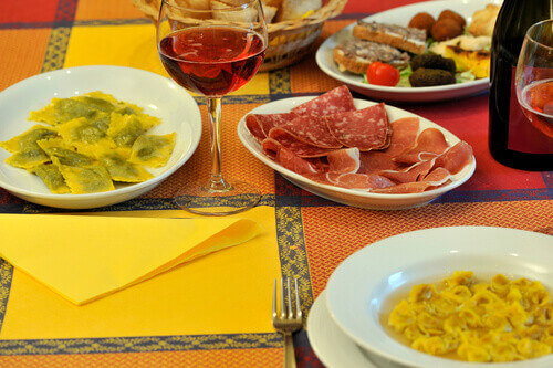 Table set with typical Italian cuisine of the Emilia Romagna region with Lambrusco wine and cured meats and tortelli in Italy