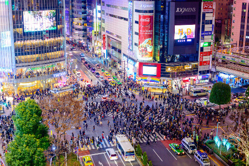 Pedestrians cross at Shibuya Crossing. It is one of the worlds most famous pedestrian crossing. Located in Tokyo, Japan