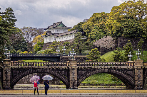 Two young ladies with umbrellas admire the striking Imperial Palace in Tokyo, Japan