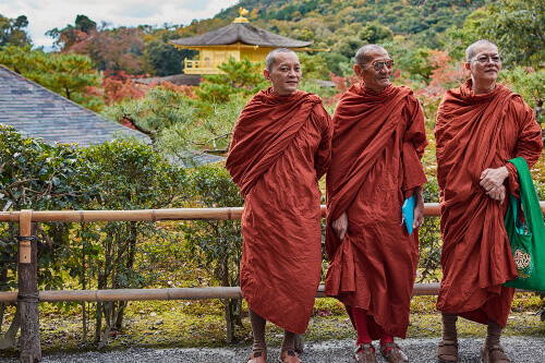 Buddhist monks standing in front of Kinkakuji temple (Golden Pavilion) UNESCO world heritage site in Kyoto, Japan