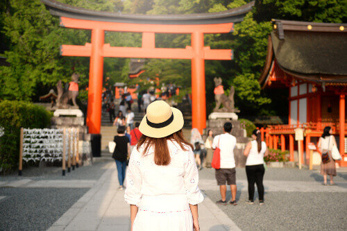 Lady tourist visiting the Fushimi Inari gate in Kyoto, Japan