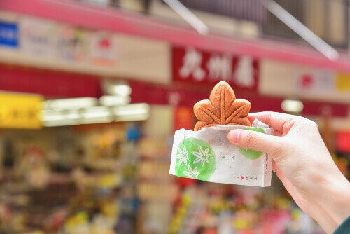Holding a Green Tea Momiji Manju or Japanese-Style Sweet Cake Filled with Green Tea Paste in Miyajima, Hiroshima, Japan