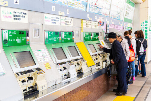 People buying tickets from machine train station Tokyo Japan
