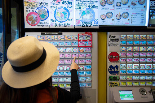 Woman selecting Japanese noodles at a vending machine in Tokyo, Japan