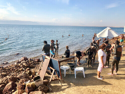 Tourists floating on a very salty water and applying mineral mud to their skin at a hotel beach on the Dead Sea in Jordan