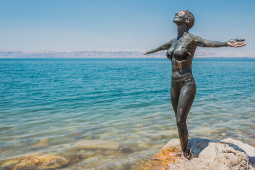 Woman with miracle mud all over on Dead Sea Shore