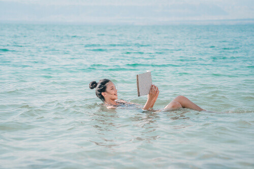 Young woman reading newspaper and floating on the surface of Dead Sea in Jordan