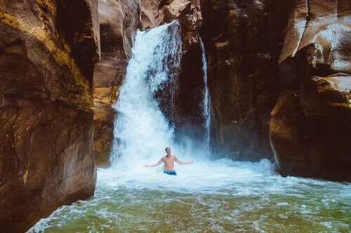 Man relaxing under a waterfall in Wadi Mujib Jordan