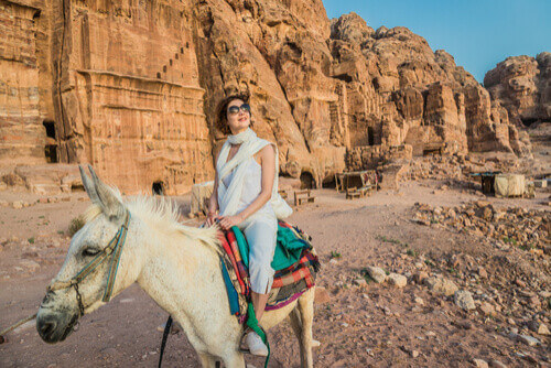 Tourist riding donkey in Nabatean Petra jordan