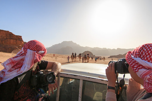 Tourists taking picture from a car driving through the Wadi Rum desert in Jordan