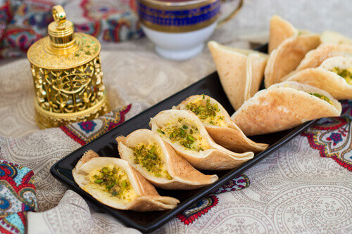 Traditional Arabic qatayf crepes stuffed with cream and pistachios prepared for iftar in Ramadan in Jordan