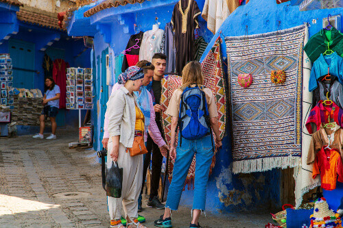 Tourists bargaining at the market in the blue city of Chefchaouen Morocco