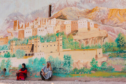 Berber woman and man sitting in front of the wall which has been painted of the cityscape of Erfoud in Erfoud Morocco
