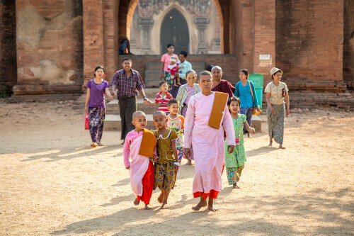Group of locals walks through one of the thousands temples of Bangan in a blue sky day in Bangan Myanmar