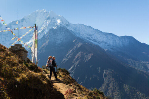 hiker standing on mountain edge with pack and prayer flags nepal