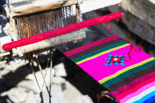 The process of handmade knitting traditional colorful yak wool shawls on the Nepalese tourist souvenir market in Himalayas Nepal