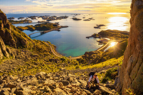 Hiker going to the top of mount Festvagtind with views over the village of Henningsvaer in Lofoten islands Norway