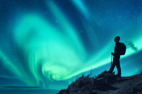 Aurora borealis and silhouette of a woman with backpack at night in Norway