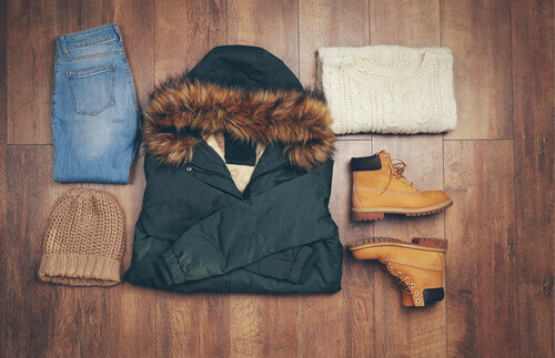 Set of beautiful winter female clothes on wooden background for Norway