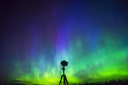Silhouette of DSLR camera on tripod in front of brilliant vibrant aurora borealis in Norway