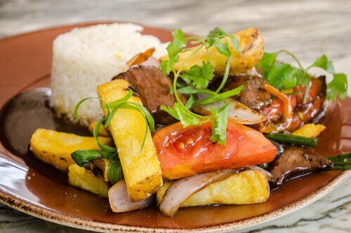 Lomo Saltado, a popular Chifa or Peruvian - Chinese stir fry dish combining marinated beef sirloin, onions, tomatoes and french fries, served with white rice in Peru