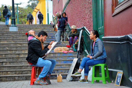 Tourist getting her face drawn in Barrio de Barranco in Lima, and arriving at its famous Bridge of Sighs in Barranco Lima Peru
