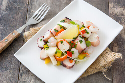 Traditional seafood ceviche or seafood salad from Peru on a plate with a wooden background