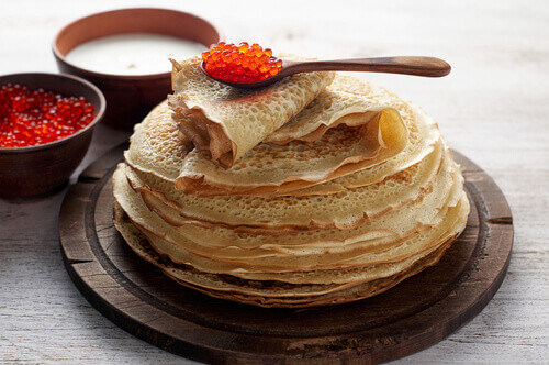 Stack of russian thin pancakes blini with red caviar and fresh sour cream