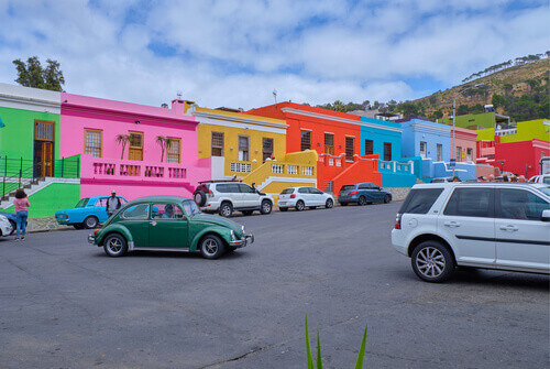 Car on the main street of colourful facades of the houses in Bo Kaap in Cape town South Africa