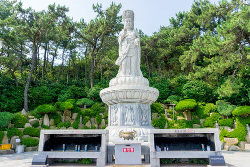 Guanyin or Guan Yin Goddess of Mercy white stone statue on the top of the hill at Haedong Yonggungsa Temple in Busan South Korea