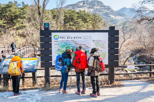Korean hikers reading the road sign of Bukhansan Mountain National park in Seoul, South Korea