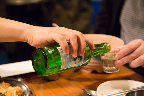 Soju pouring from bottle into glass at the party in Seoul South Korea