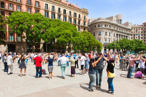 People holding hands and dancing the national catalonian dance called Sardana at a Plaza in Barcelona Spain