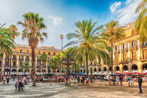 People walking in Placa Reial or Plaza Real a scenic and iconic square of the Gothic Quarter in Barcelona Catalonia Spain