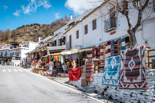 Capileira town in Alpujarras wit street market selling different kinds of souvenirs in Sierra Nevada, Andalusia, Spain
